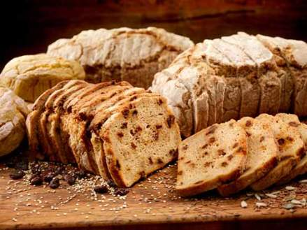 Assorted gluten free breads sliced on a wooden cutting board.