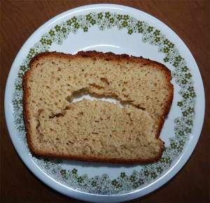 Slice of gluten-free bread on a plate, with a hole in the middle of the slice.