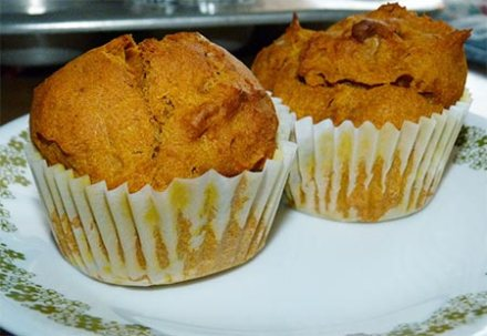 Close up of two pumpkin muffins on plate.