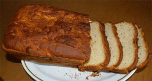 Loaf of gluten-free bread with a few slices on a plate.