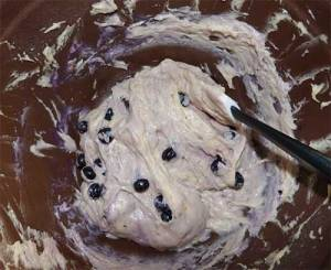 Gluten-free blueberry muffin batter in bowl with blueberries being stirred in.