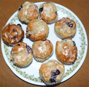 Nine glazed blueberry muffins on plate.