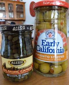 Capers and green olives in jars.