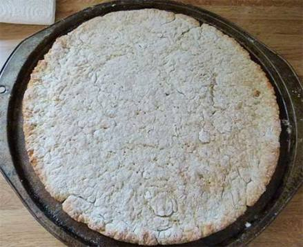 Gluten-free pizza crust in pan after cooking for 10 minutes - ready to put on the toppings.