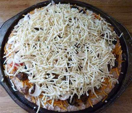 Pizza crust with toppings added and Daiya cheese - ready to cook.
