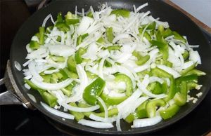 Sliced peppers, onion and garlic in skillet on stove.