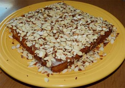 Finished cake on yellow platter with glaze and almonds.