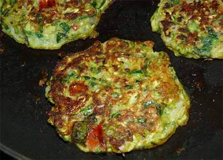 Close-up of zucchini fritter in frying pan after flipping over.