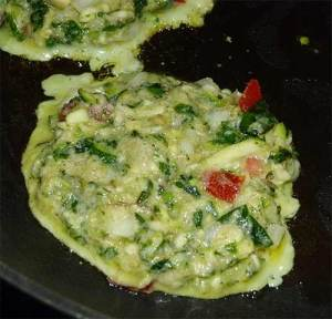 Close-up of zucchini fritter frying in the frying pan