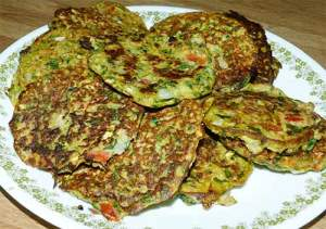 Zucchini fritters piled up on a plate.