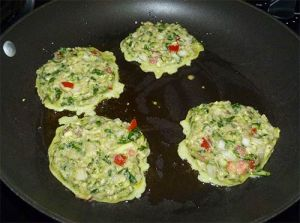 Four zucchini fritters cooking in frying pan.