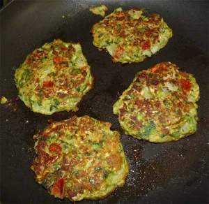 Four zucchini fritters cooking in frying pan flipped over with crispy side up.