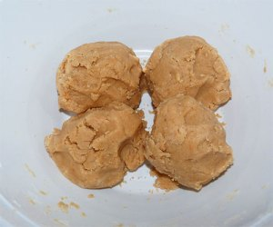 Four large balls of peanut butter cookie dough in a large white bowl.