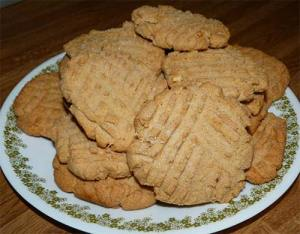 Finished peanut butter cookies piled up on a large dinner plate.