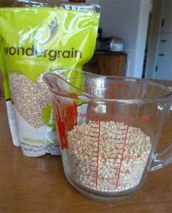Bag of Wondergrain whole grain sorghum next to glass measuring cup holding sorghum grains.