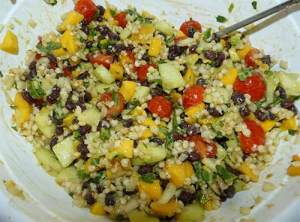 Sorghum salad with all ingredients mixed together in a white bowl.