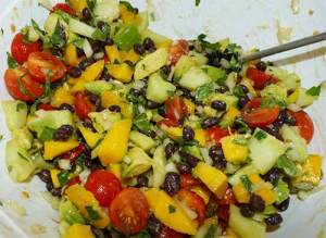 All vegetables and fruit chopped up and mixed together in a white bowl