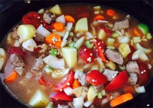 Beef, vegetables, broth and whole grain sorghum in the slow cooker.