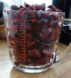 Two-cup glass measuring cup full to the top of pitted Bing cherries