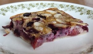 Slice of cherry clafouti on dessert plate, view from side.