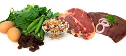 An assortment of iron-rich foods: eggs, spinach, beans, prunes, steak and liver.
