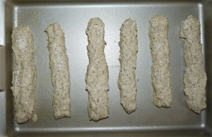 Six breadsticks uncooked in baking pan.