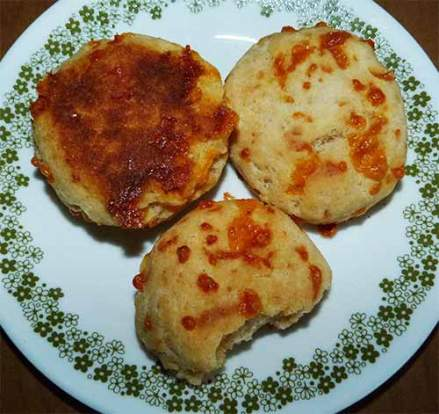 Three cheese biscuits on plate, one has a bite taken out of it.