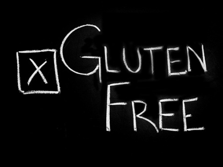 "The words ""Gluten Free"" written on a black chalk board with a check box in front that has an ""X"" in it."