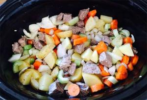 Browned beef and cut up vegetables in the slow cooker.