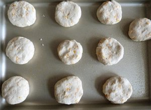 Ten uncooked cheese biscuits on tray ready to cook.