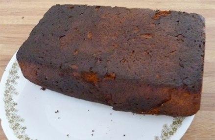 Gluten-free pound cake upside down on plate showing a slightly burned bottom.