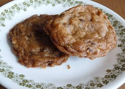 Closeup of two gluten-free chocolate chip cookies on a dessert plate.