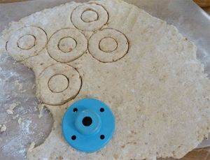 Rolled out dough with doughnut cutter on top, some shapes already pressed out.