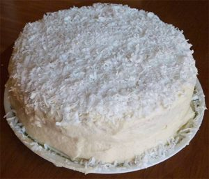 Finished layer cake with white butter frosting applied and shredded coconut spread over the top.