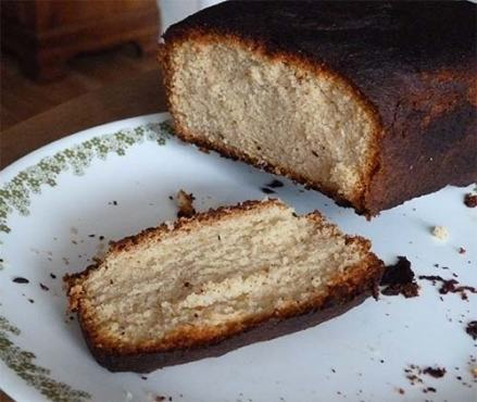 Slice cut off of gluten-free pound cake, on a plate, showing nice yellow cake in the middle.