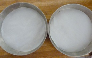 Two round cakes pans with round pieces of parchment paper in the bottom of each one.
