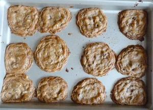 Baked chocolate chip cookies on baking sheet.