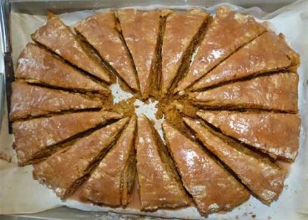 Gluten-free pumpkin scones on cookie sheet with glaze on top.