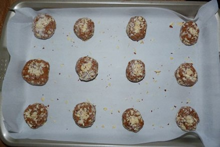 Twelve balls on ginger cookie dough rolled in sugar-almond mixture on baking sheet with parchment paper underneath ready to bake.