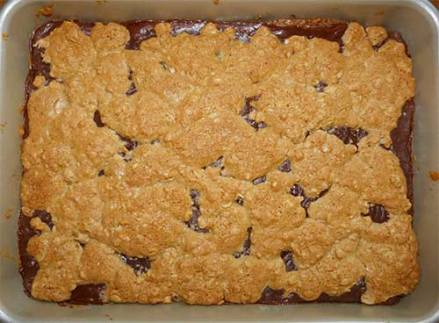 Baking pan with cooked oat fudge bars - topping has spread out almost covering the chocolate.