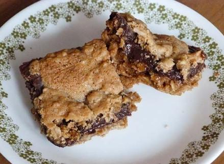 Two gluten-free oat fudge bars on a dessert plate. One bar is turned up so you can see the chocolate filling.