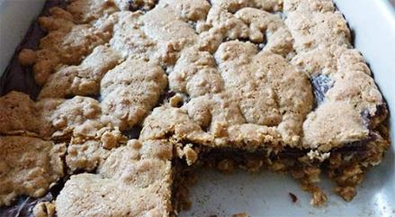 Oat fudge bars in pan with 2 pieces removed so you can see the chocolate filling.