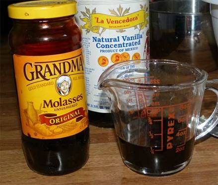 Measuring cup with molasses next to a jar of Grandma's molasses with a large bottle of vanilla behind.