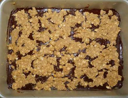 Baking pan with all layers of oats and chocolate filling, ready to put in the oven.