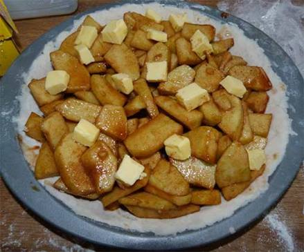 Apple and spice mixture in bottom pie crust with pieces of butter on top.