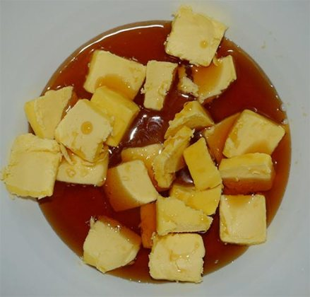 White mixing bowl containing sugar, chunks of butter and maple syrup.