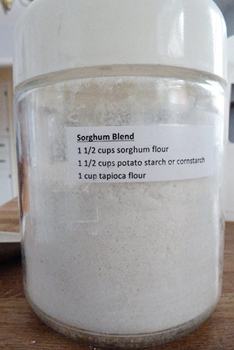 Glass canister containing sorghum flour blend with recipe for it taped to the front.