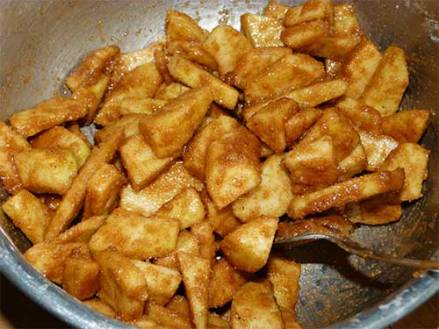 Sliced apples in a bowl coated with sugar and spices.
