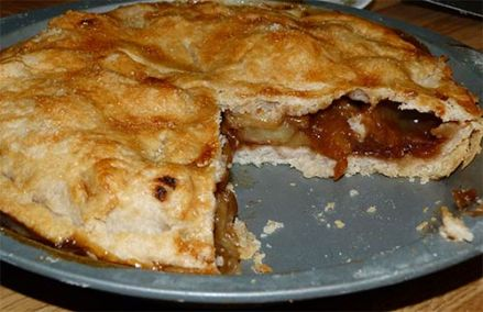 Gluten-free apple pie with slice cut out so you can see the filling and the bottom crust.