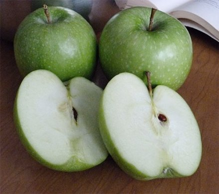 Two whole Granny Smith apples and one cut in half.